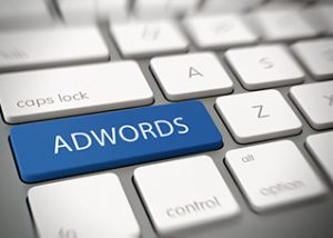 48326265 - adwords online advertising concept with white text - adwords - on a large blue enter key on a white computer keyboard viewed obliquely at a high angle with blur vignette